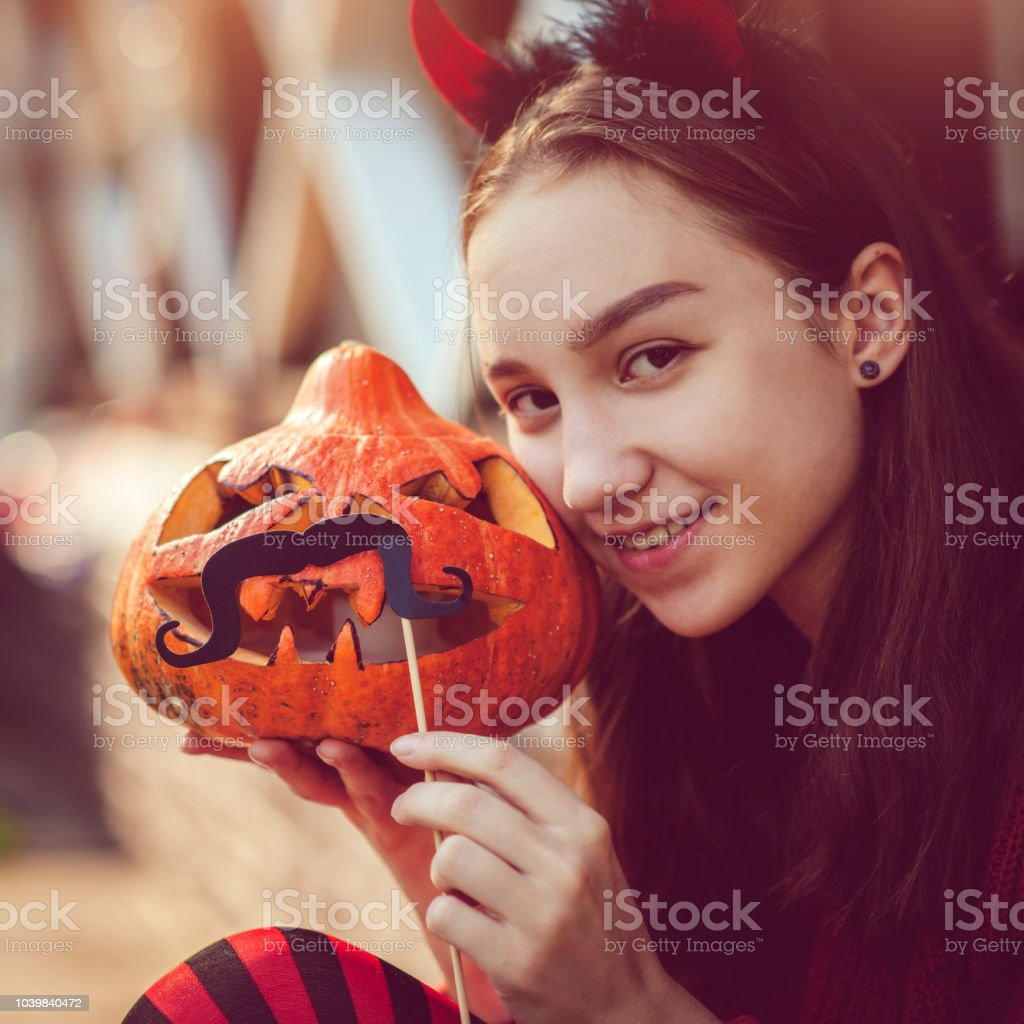 Girl holding jack o' lantern with moustache stock photo