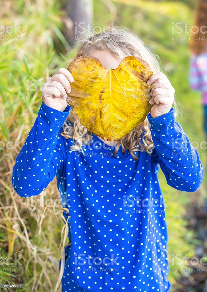 Girl Holding Large Leaf In Front of Her Face foto stock royalty-free