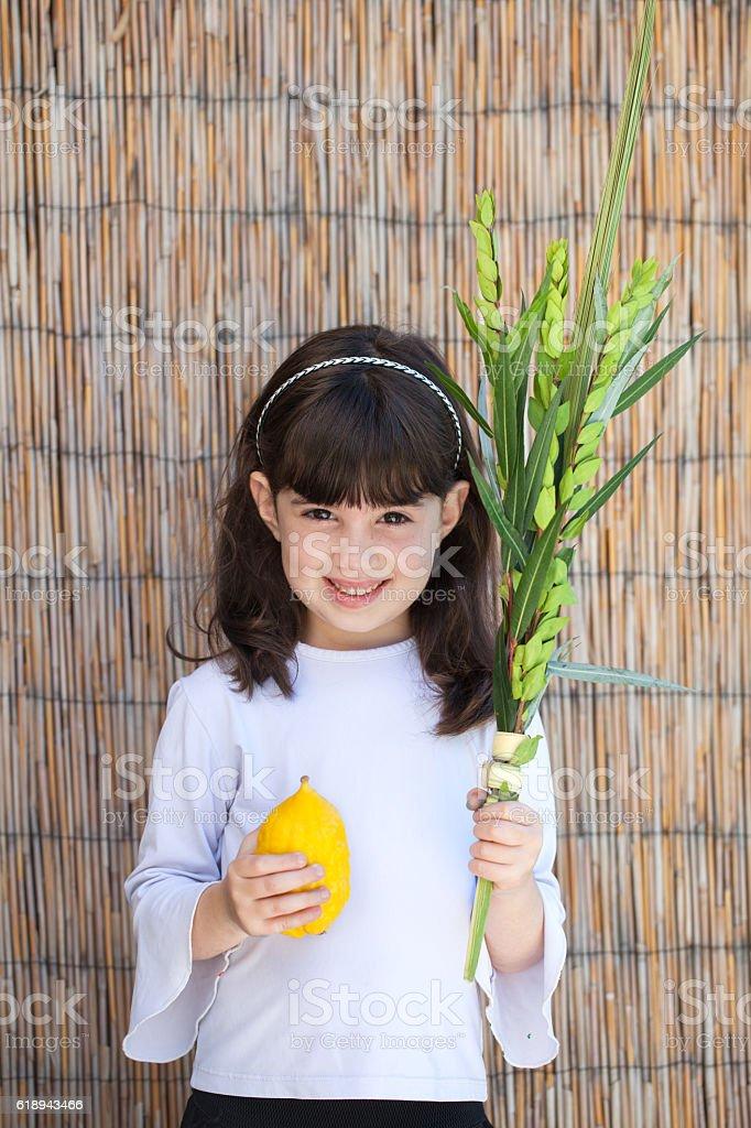 Girl holding lulav and etrog for Sukkot stock photo