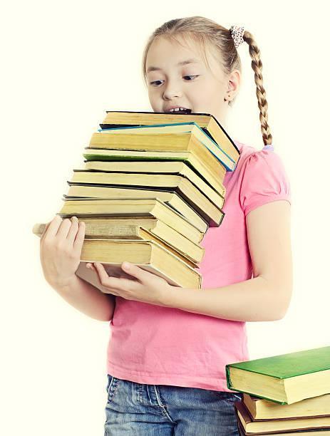girl holding many books stock photo