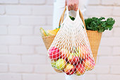 Girl holding mesh shopping bag full of apples and straw bag with organic vegetables, brick background. Zero waste, plastic free concept. Sustainable lifestyle. Copy space.