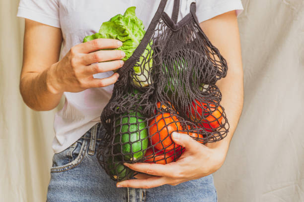 Girl holding mesh shopping bag full of vegetables and taking from inside a fresh lettuce from the farm. Sustainable, zero waste and plastic free lifestyle. Save the planet concept stock photo