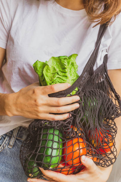 Girl holding mesh shopping bag full of vegetables and taking from inside a fresh lettuce from the farm. Sustainable, zero waste and plastic free lifestyle. stock photo
