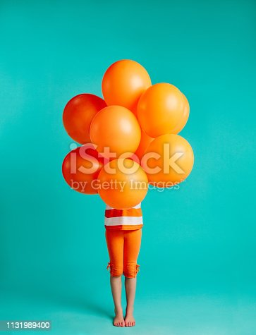 Girl holding orange balloons in front on blue background. Full length of small girl child with bunch of helium balloons.