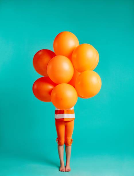 mädchen, die orangefarbene luftballons vor sich halten - kinderfarben stock-fotos und bilder
