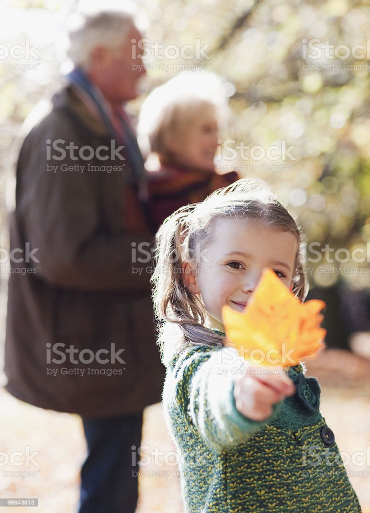 Girl holding out autumn leaf royalty-free stock photo