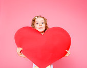 Lovely curly little girl holding large paper heart, over pink background