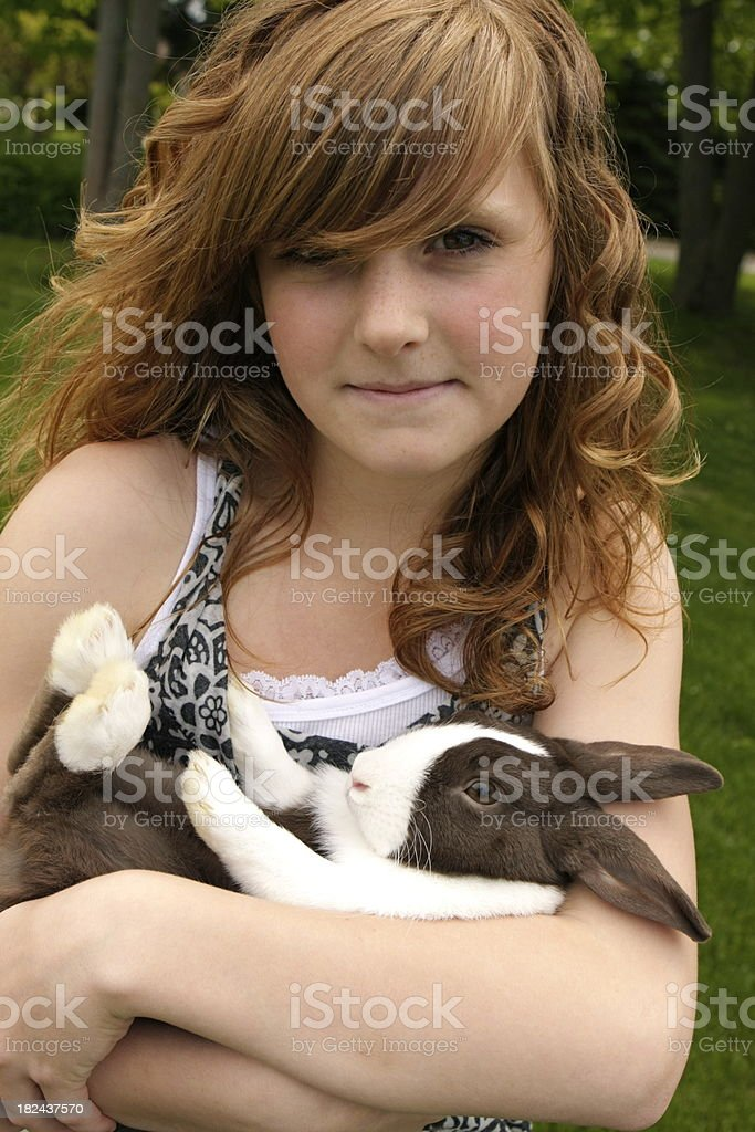 A beautiful 13 year old girl cradles her pet rabbit in her arms. Shot...