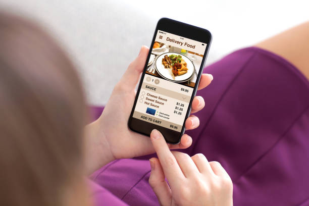girl holding phone with app delivery food on screen - food delivery стоковые фото и изображения