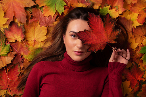 istock Girl holding red maple leaf in hand over colorful fallen leaves background. Sunny day, warm weather. Gold cozy autumn concept. Top view. Copy space 1147535584