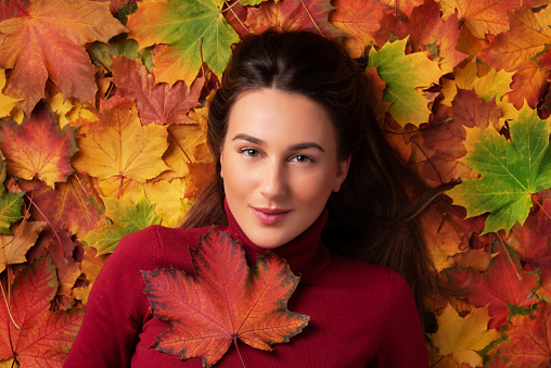 istock Girl holding red maple leaf in hand over colorful fallen leaves background. Top view. Copy space for advertising. Sunny day, warm weather. Gold cozy autumn concept 1147535571