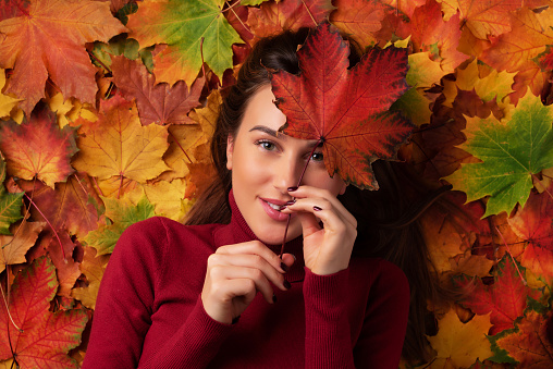 istock Girl holding red maple leaf in hand over colorful fallen leaves background. Top view. Copy space for advertising. Sunny day, warm weather. Gold cozy autumn concept 1147535572