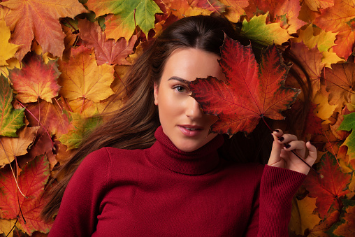 istock Girl holding red maple leaf in hand over colorful fallen leaves background. Top view. Copy space for advertising. Sunny day, warm weather. Gold cozy autumn concept 1147535576