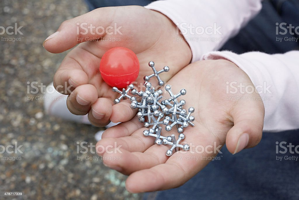 Girl Holding Rubber Ball And Jacks stock photo
