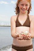 Girl holding seashells on the beach