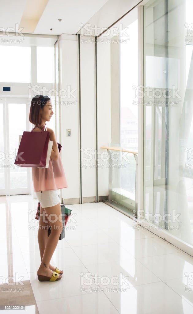 girl holding shopping bags look shopwindow stock photo