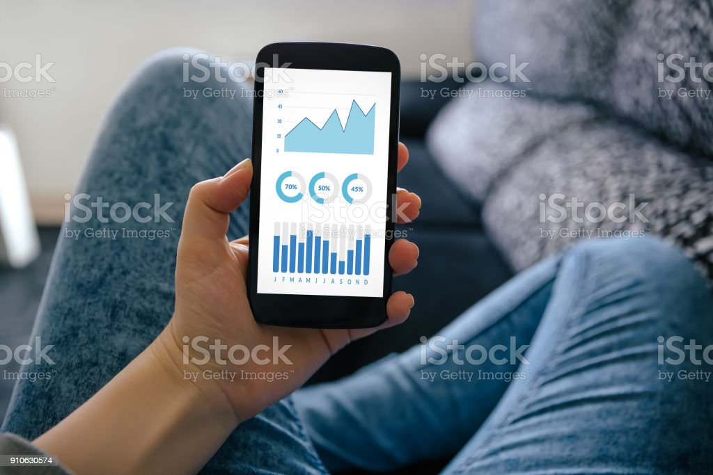 Girl holding smart phone with graphs and charts elements on screen stock photo