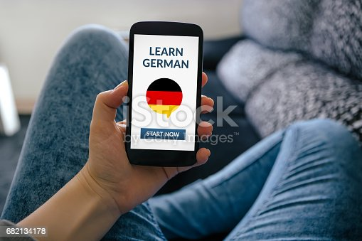 istock Girl holding smart phone with learn german concept on screen 682134178