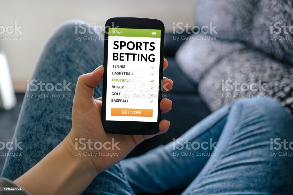 Girl holding smart phone with sports betting concept on screen stock photo