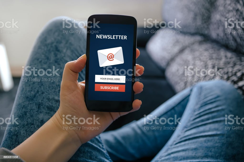 Girl holding smart phone with subscribe newsletter concept on screen