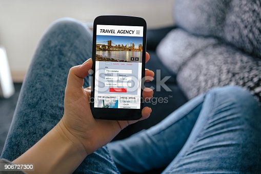 Girl holding smart phone with travel agency concept on screen. All screen content is designed by me
