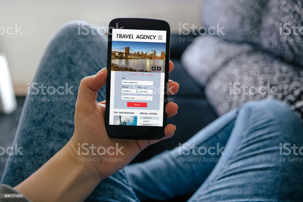 Girl holding smart phone with travel agency concept on screen stock photo