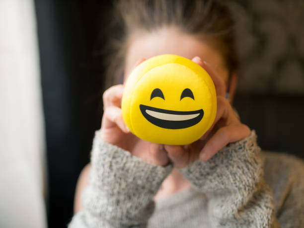 Jeune fille tenant le visage de smiley, emoticon devant son visage en riant - Photo