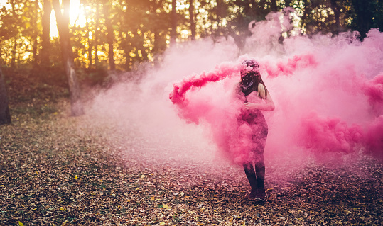 Young caucasian girl with scarf on her face holding smoke fountain in the forest.