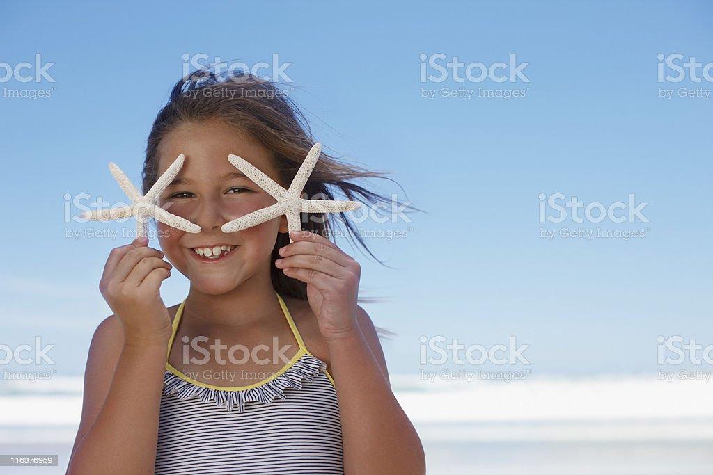 Girl holding starfish on beach stock photo