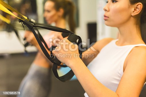 istock Girl holding strap during suspension training in the gym 1092680578
