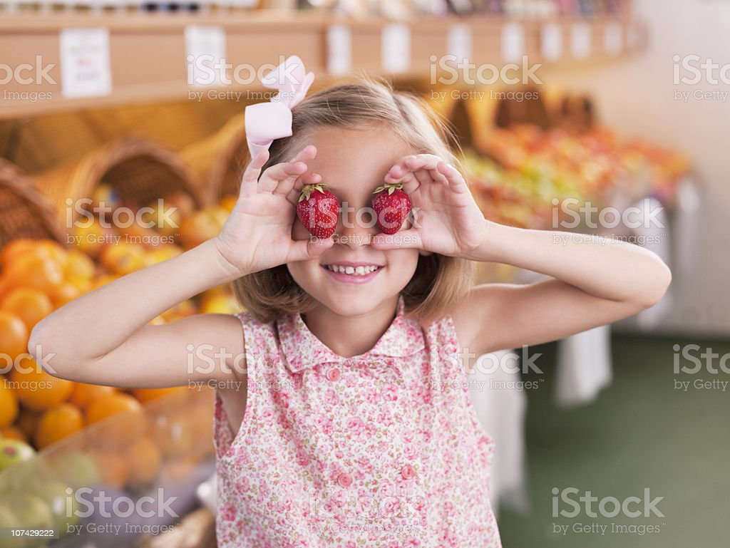 Girl holding strawberries in front of eyes in grocery store royalty-free stock photo