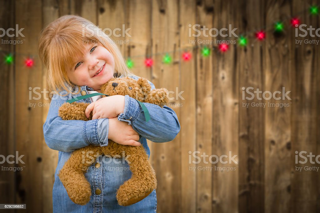 Girl Holding Teddy Bear In Front of Christmas Lights stock photo