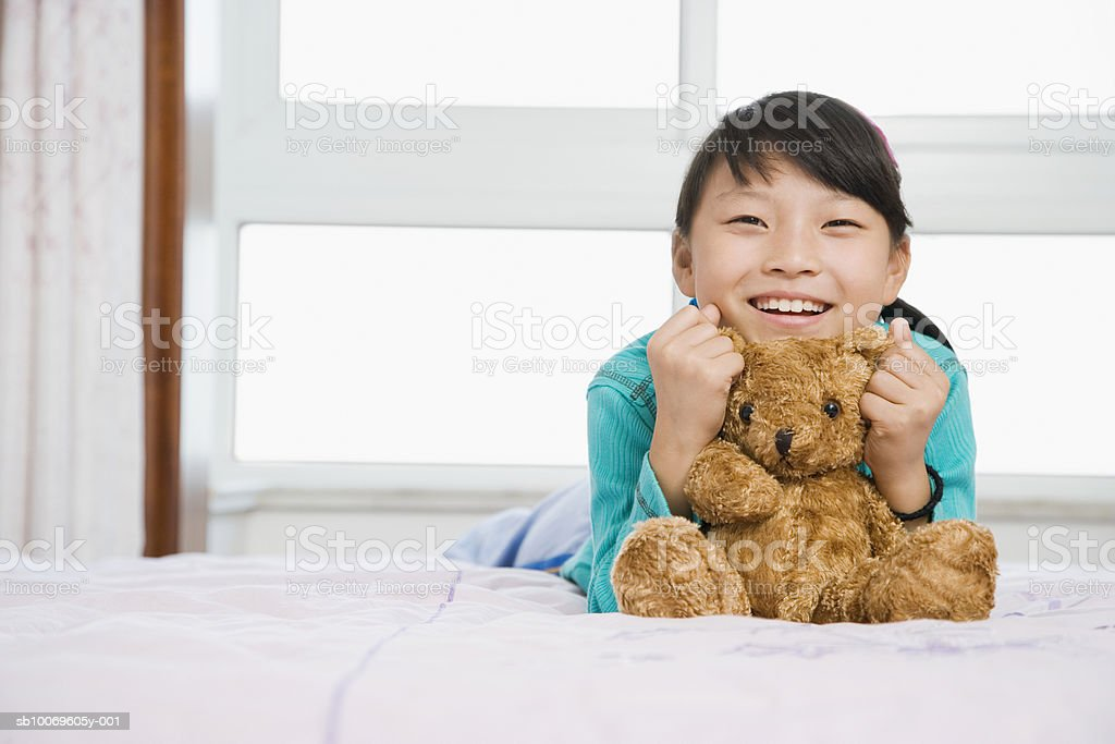 Girl (8-9) holding teddy bear, smiling, portrait photo libre de droits