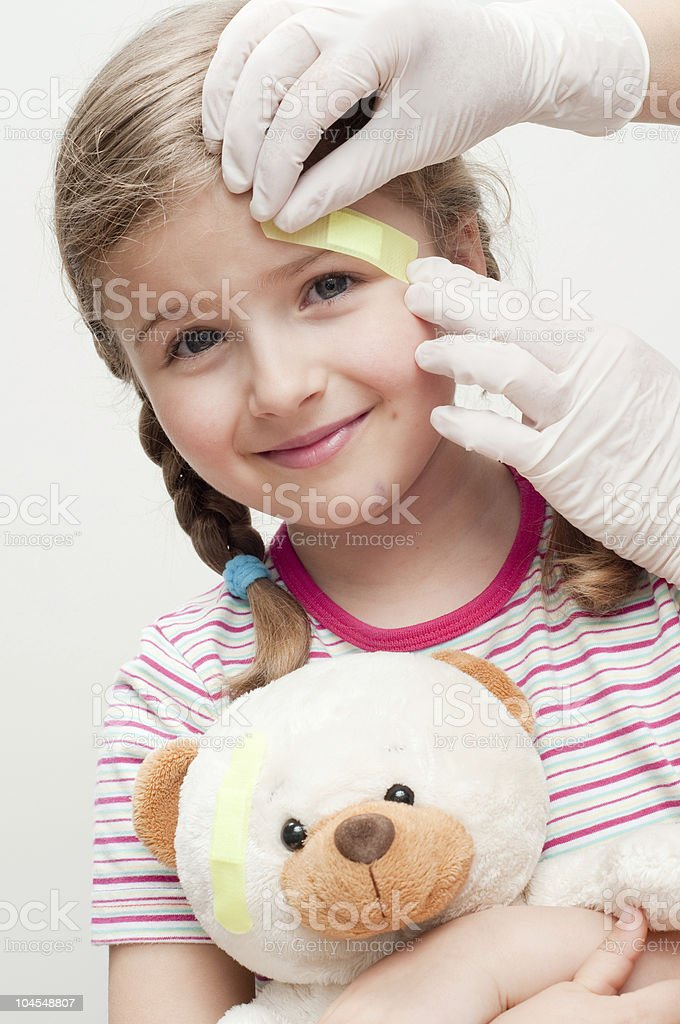Girl holding teddy with latex glove applying plaster to head royalty-free stock photo