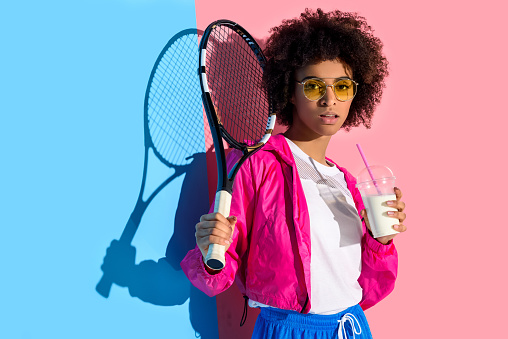Young bright african american girl holding tennis racket and plastic cup with drink on pink and blue background