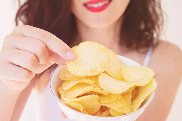 A girl holding the big potato chips bowl. Asking to eating together, Happiness sharing concept. stock photo