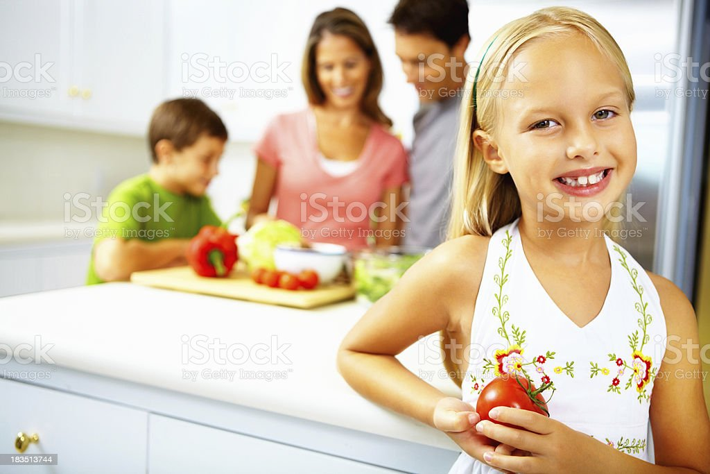 Girl holding tomato while family preparing food in background royalty-free stock photo