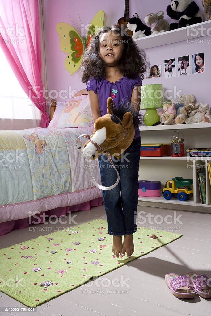 Girl (4-5) holding toy and jumping, portrait royalty free stockfoto