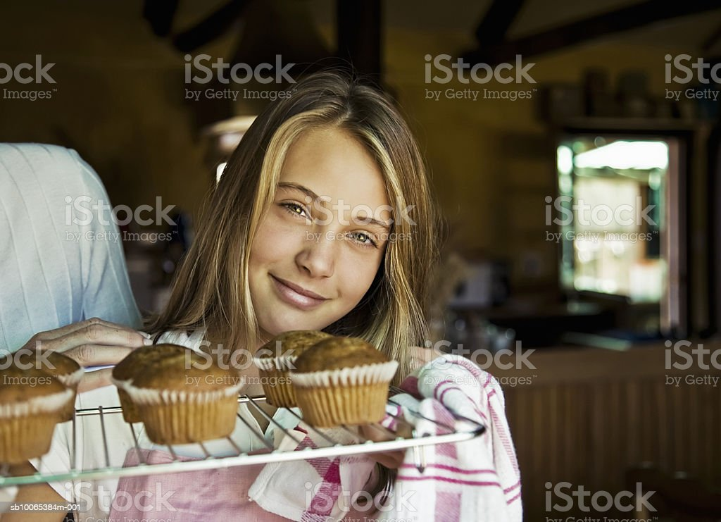 Girl (12-13) holding tray of baked cupcakes, portrait royalty-free stock photo