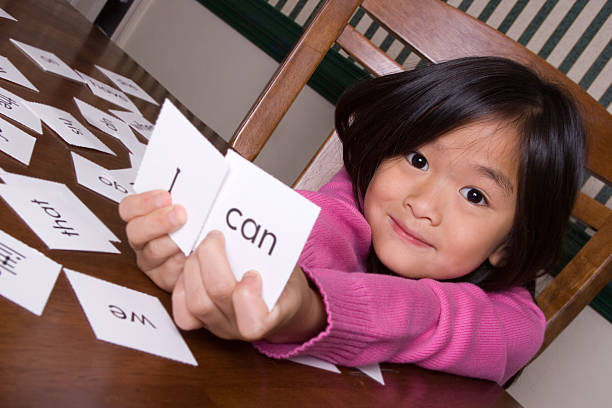 Girl holding up flash cards that say 'I' and 'can' stock photo