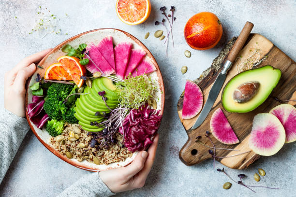 girl holding vegan, detox buddha bowl with quinoa, micro greens, avocado, blood orange, broccoli, watermelon radish, alfalfa seed sprouts. - vegetariano foto e immagini stock
