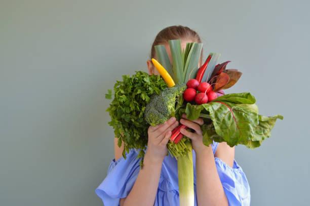 chica sosteniendo ramo de verduras - vegana fotografías e imágenes de stock