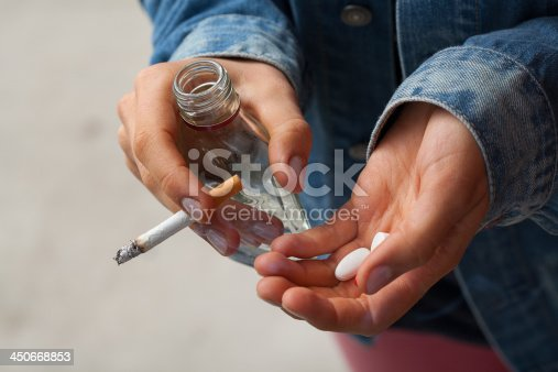 istock Girl holding vodka,pills and cigarettes 450668853