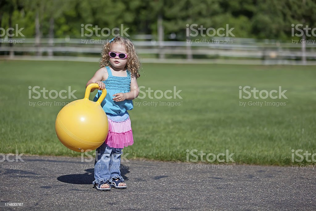 Girl Holding Yellow Bouncy Ball royalty-free stock photo