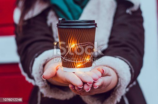 A girl holds a cup of coffee. Around the New Year's atmosphere and lights of a garland.