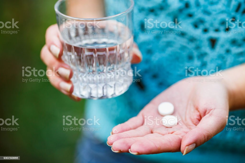 girl holds a glass of clean water and two white pills stock photo