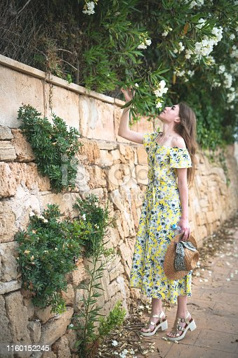 girl with hat holds a growing branch of flowers on a stone wall and sniffs them