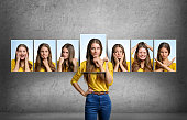istock Girl holds and changes her face portraits with different emotions 518951630
