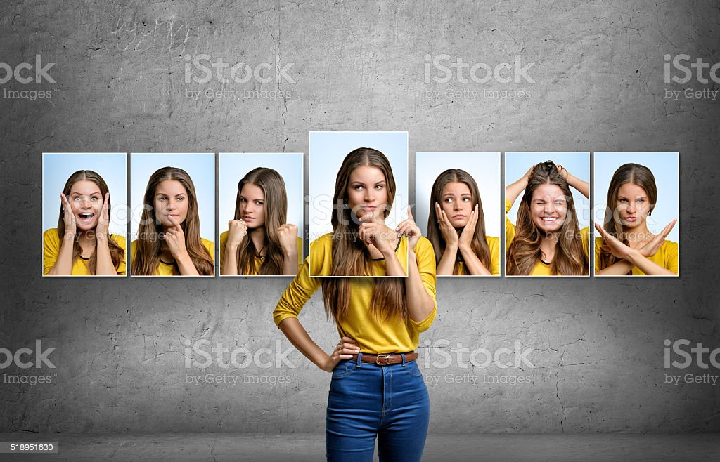 Girl holds and changes her face portraits with different emotions stock photo