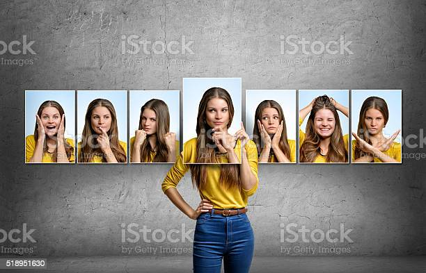 Young beautiful girl holds and changes her face portraits with different emotions.